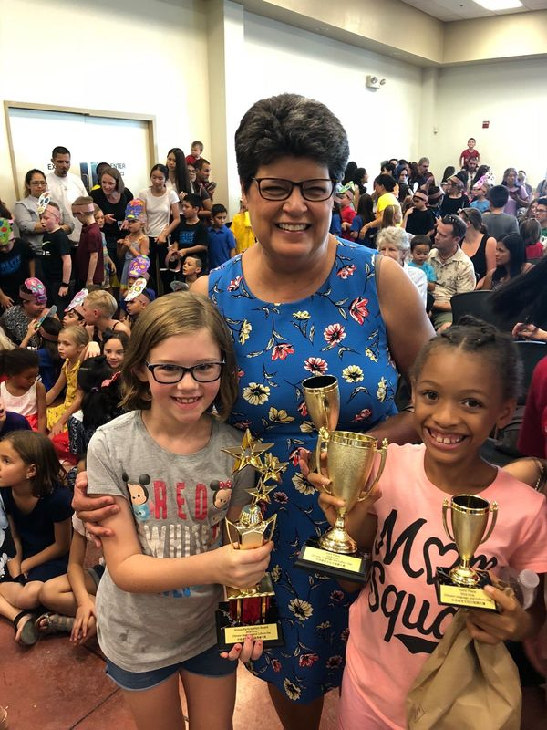 Mrs. Davidson with kids holding trophies